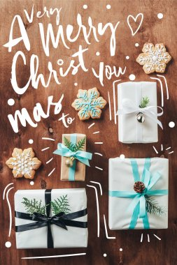 top view of gift boxes and christmas cookies with icing on wooden background with