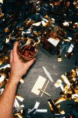 partial view of man with whiskey glass near cocaine with rolled banknote and credit card on table covered by golden confetti
