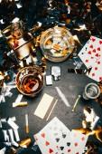 Blick von oben auf Spielkarten, Zigaretten, Whiskey, Geldscheine, Kreditkarte und Kokain auf einem mit goldenem Konfetti bedeckten Tisch