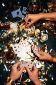 Teilansicht von Männern, die Zigaretten rauchen und Poker am mit goldenem Konfetti bedeckten Tisch spielen