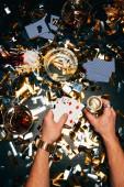 Teilansicht eines Mannes mit Spielkarten und Alkohol, der am mit goldenem Konfetti bedeckten Tisch sitzt