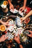 Oříznout záběr přátel s alkoholickými koktejly hrát poker u stolu se vztahuje zlaté konfety
