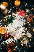 elevated view of playing cards, alcoholic cocktails with orange slices, whiskey and party horns on table covered by golden confetti