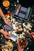 Teilansicht der Frauen Pokern am Tisch mit Whisky, alkoholischen Cocktail und Zigaretten und goldenen Konfetti