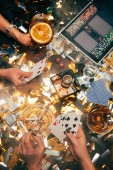 cropped image of women playing poker at table with whiskey, alcoholic cocktails and cigarettes and golden confetti