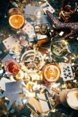 erhöhter Blick auf alkoholische Cocktails, Spielkarten, Zigaretten, Geldscheine, Kreditkarten und Kokain auf einem mit goldenem Konfetti bedeckten Tisch