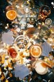 Fotografie flache Lay mit Zigaretten, alkoholische Cocktails, Whiskey und Spielkarten auf Tisch fallenden goldene Konfetti