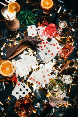 top view of female shoes on high heels, playing cards, alcoholic cocktails and party horns on table covered by golden confetti