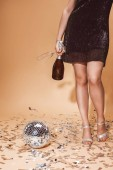 cropped image of woman holding empty glass and bottle of champagne at party on beige