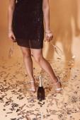 Fotografia immagine potata della donna che tiene bicchieri vuoti, bottiglia di champagne sul pavimento con i coriandoli su beige