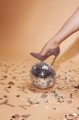 Fotografie ořízne obraz žena dát nohu na stříbrné disco koule, konfety na podlaze