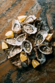 Photo food composition of oysters, lemon pieces and ice on grungy tabletop