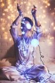 Fotografie Žena v pyžamu položenou na posteli s vánoční osvětlení okolí