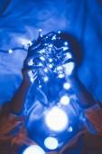 Fotografie zakryt pohled ženy držící modrých světel v rukou vleže na posteli
