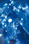 Fotografie částečný pohled ženy v pyžamu na posteli s modré slavnostní osvětlení okolí