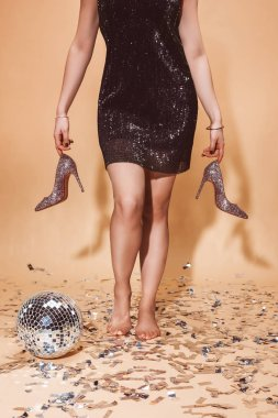 cropped image of woman walking on floor with confetti and holding high heels at party on beige