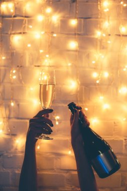 partial view of woman holding glass and bottle of champagne in hands with christmas lights behind