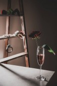 rote Rosenblüten in Champagner-Glas am Steintisch mit Holzleiter und Metall Handschellen auf Hintergrund