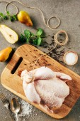 top view of raw chicken on cutting board with pears and greenery