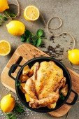 top view of fried chicken in griddle pan with lemons and greenery