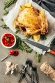 fried chicken with lemons on cloth with knife, sauce,forks and rosemary