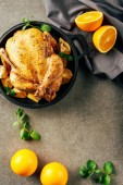 top view of fried chicken in griddle pan with oranges, greenery and cloth