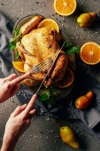 cropped view of woman cutting fried chicken with oranges, pears and greenery on tray