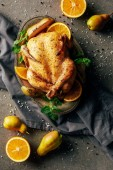 top view of fried chicken with oranges, pears and greenery on tray and cloth