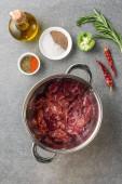 Fotografia vista superiore di carne cruda in pentola, spezie, olio, peperoni, broccoli e rosmarino