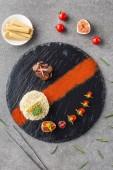 pohled shora z rýže, brokolice, fíkovníky a smažené maso na černém plátu s kuří oka a cherry rajčátky