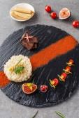 Reis, Brokkoli, Feigen und gebratenes Fleisch auf schwarzem Teller mit Hühneraugen und Kirschtomaten