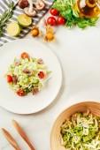 salát, zelí a celer v desce s lahví olej, cherry rajčátky, vápna a houby