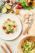 insalata, cavolo e sedano in lamiera con bottiglia di olio, pomodorini, limes e funghi sul tagliere