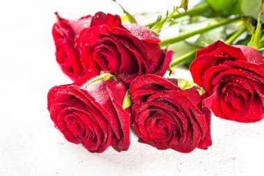 Red roses flower bouquet on white background top view.