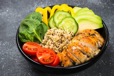 Buddha bowl quinoa salad with chicken and vegetables on black.