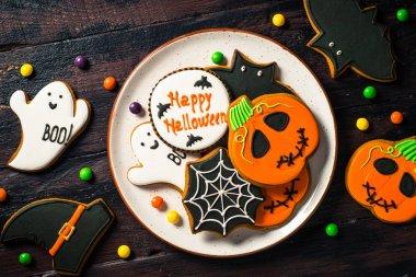 Halloween Gingerbread Cookies - pumpkin, ghosts, bat, on woden table.