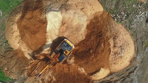 The crawler excavator moves the sand to the shoulder.