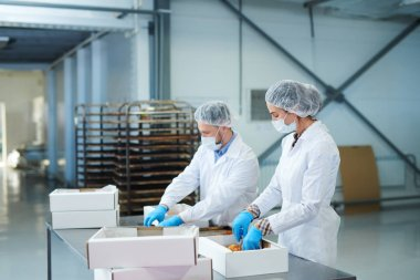 Confectionery factory workers in white coats putting ready pastry into paper boxes.