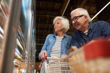 Low angle portrait of modern senior couple grocery shopping in supermarket, smiling happily while choosing frozen foods standing by freezers