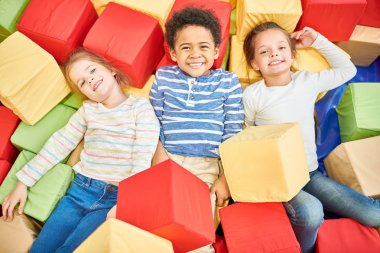 Colorful above view portrait of three happy little kids playing in foam pit of trampoline center