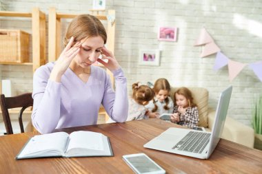 Tired young woman suffering from terrible headache wrapped up in work while her little daughters sitting on cozy sofa and playing game on digital tablet, interior of living room on background