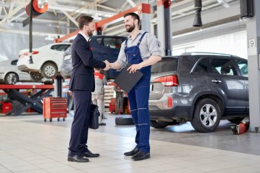 Full length portrait of handsome businessman shaking hands with workman while standing in production workshop of modern car factory, copy space