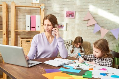 Pretty young woman discussing project details with colleague and taking necessary notes on laptop while working from home, her little daughters taking rest at living room