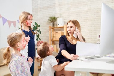 Cheerful little sisters smeared with red lipstick standing at their mother, she distracted from phone call and looking at them amazedly, interior of living room on background