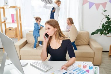 Waist-up portrait of pretty young freelance worker discussing order details with client while using smartphone, her little children wrapped up in pillow fight, interior of living room on background