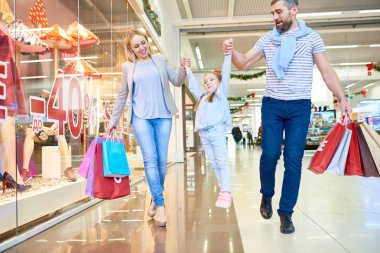 Full length portrait of carefree family shopping in mall walking past window displays with red sale signs