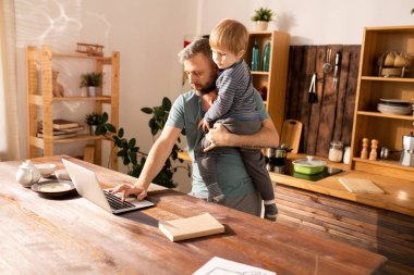 Serious thoughtful handsome bearded single father holding little son and typing on laptop while working at home
