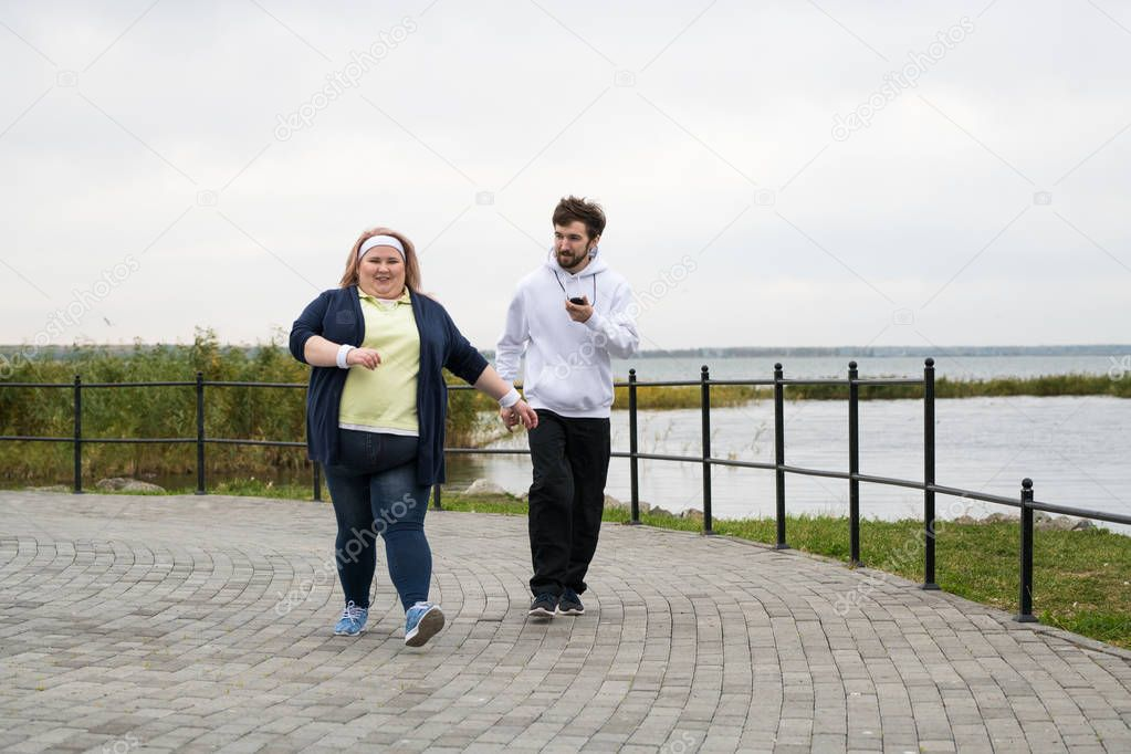 Full length portrait of overweight woman running outdoors with personal trainer, copy space