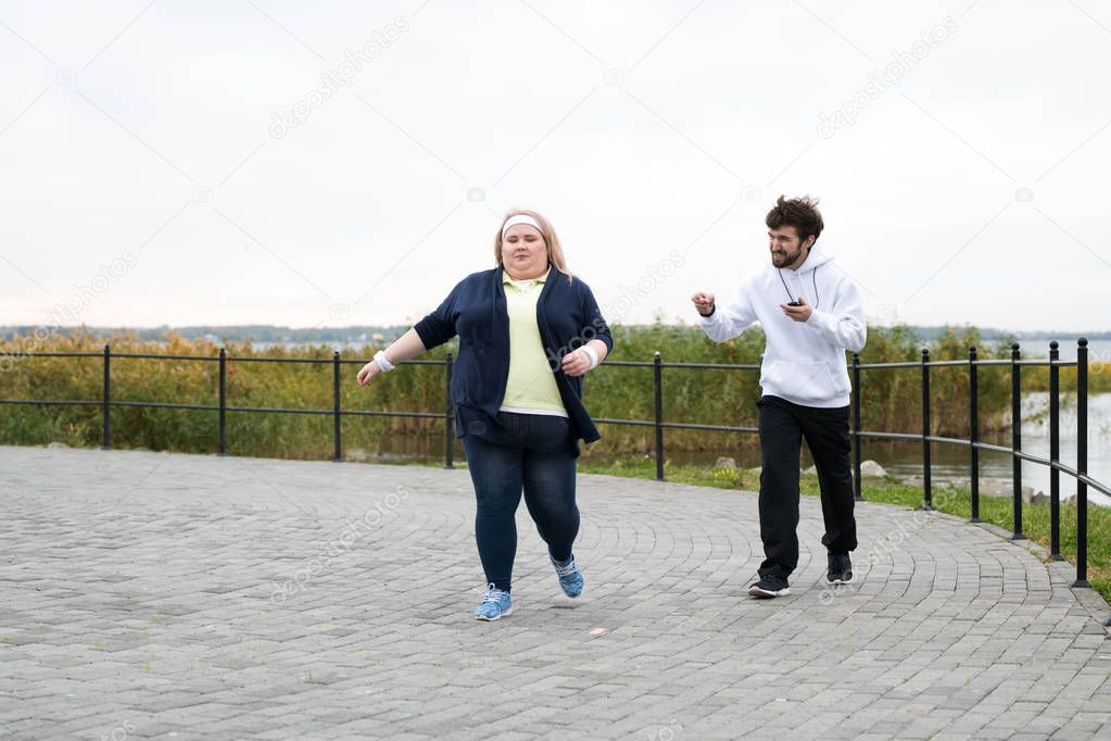 Full length portrait of obese young woman running outdoors with personal trainer motivating her, copy space