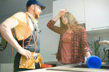 Exhausted young woman with curly hair wiping forehead and holding plunger while talking to young plumber in cap wearing tool belt, woman having clogged drains in kitchen
